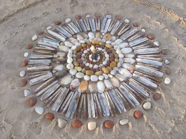 A beach mandala by Therese Muskus made from stones and shells