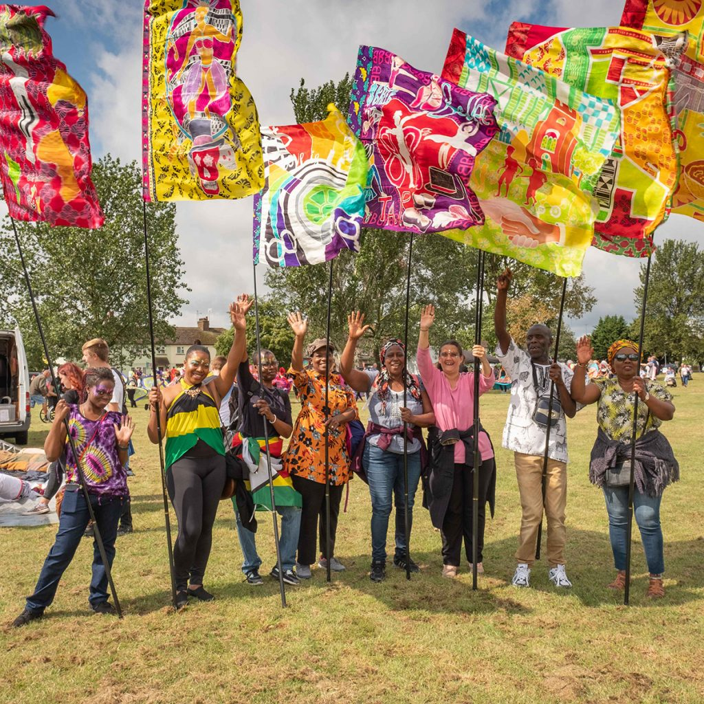 Members of One Community Development Trust waving colourful flags