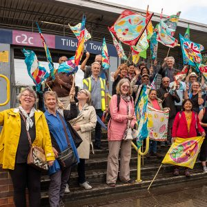 A group of people waving flags outside Tilbury station